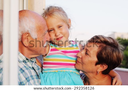 grandfather and grandmother holding  4 years old granddaughter - stock photo