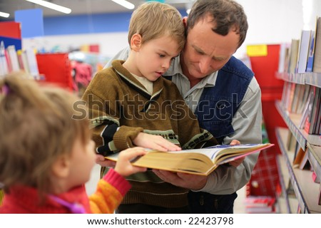 Grandfather and grandson and little girl read the book in a bookshop