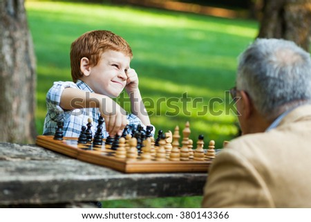 Grandfather and grandson are playing chess in park - stock photo