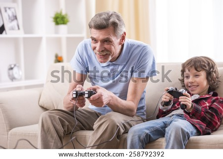 Grandfather and grandson are playing video games at home. - stock photo
