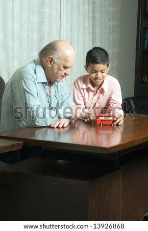 Grandfather and Grandson are seated at a table looking at a red double decker bus. Vertically framed photograph. - stock photo