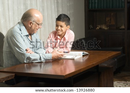 Grandfather and grandson are sitting at the table reading a book. Grandfather smiles as he reads the book to his grateful grandson. This is a horizontally framed photo. - stock photo