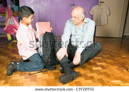 Grandfather and grandson are sitting on the floor as grandson gets ready for school. Grandfather watches all grandsons actions as he packs his bag for school. This is a horizontally framed photo. - stock photo