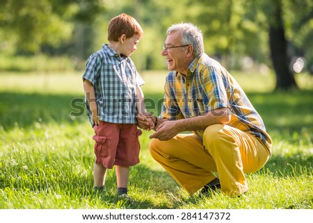 Grandfather and grandson are talking in park  - stock photo