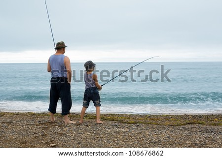 Grandfather and grandson fishing at the weekend at sea. Early in the morning. - stock photo