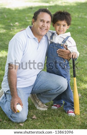 Grandfather and grandson holding baseball bat and smiling - stock photo