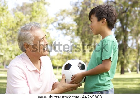 Grandfather And grandson In Park With Football - stock photo