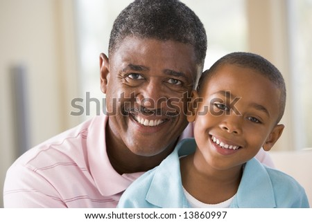 Grandfather and grandson indoors smiling - stock photo