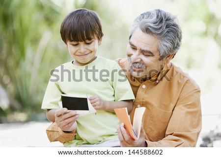 Grandfather and grandson looking at photographs - stock photo
