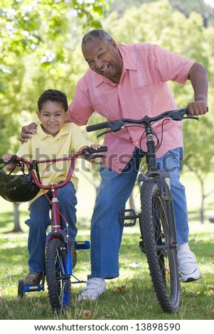 Grandfather and grandson on bikes outdoors smiling - stock photo