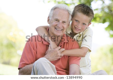 Grandfather and grandson outdoors smiling - stock photo