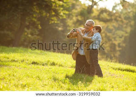 Grandfather and grandson photographing nature in park - stock photo