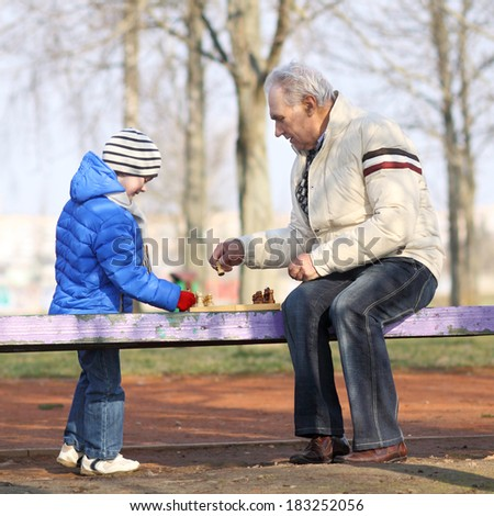 Grandfather and grandson playing chess. Grandfather and grandchild - stock photo