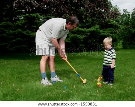 Grandfather and grandson playing croquet - stock photo