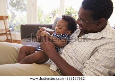 Grandfather And Grandson Playing Game On Sofa At Home