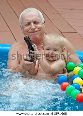 Grandfather and grandson relaxing in swimming pool, with colorful balls. Lifestyle family picture. - stock photo