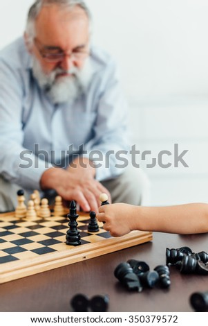 Grandfather and grandson setting a chess piece on the chessboard - stock photo