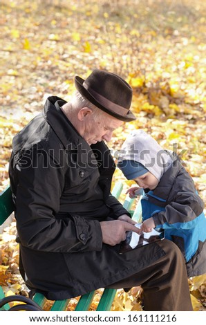 Grandfather and grandson sharing a tablet-pc surfing the internet together as they enjoy a day out in the fresh air at the park on a cold autumn day - stock photo
