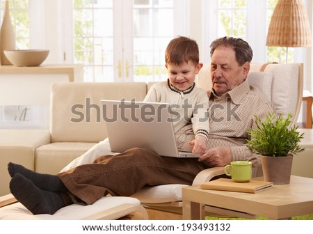 Grandfather and grandson sitting in armchair and using computer together, smiling.