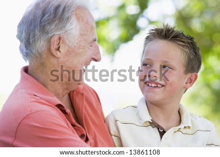 Grandfather and grandson smiling outdoors - stock photo