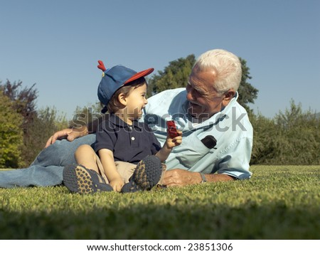 Grandfather and grandson smiling over the grass - stock photo