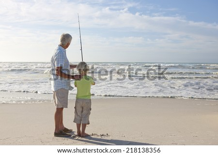 Grandfather and grandson with fishing rod on sunny beach - stock photo