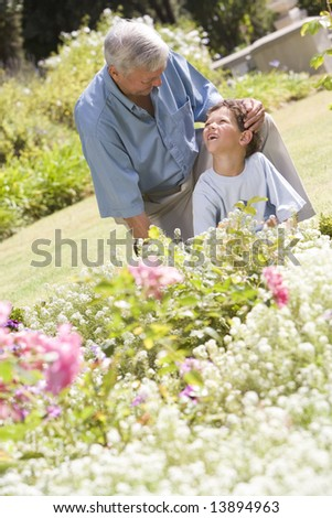 Grandfather and grandson working in the garden