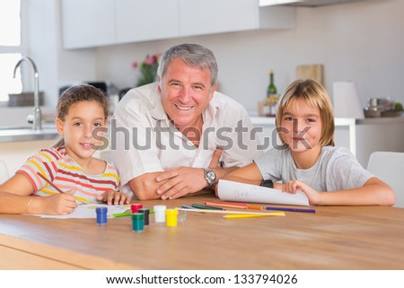 Grandfather and her grandchildren smiling at the camera with drawings in kitchen - stock photo