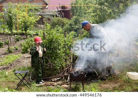 Grandfather and his grandson preparing barbecue at backyard