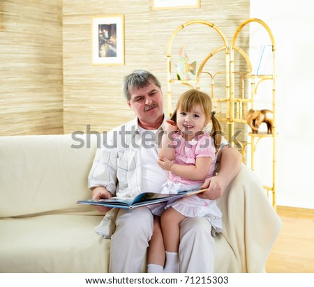 grandfather and his little granddaughter together reading a book - stock photo