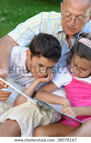 Grandfather and kids reading book - stock photo