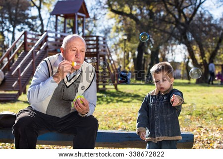 grandfather blowing soap bubbles to grandchild - stock photo