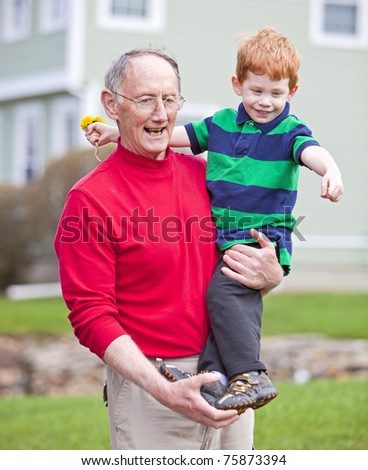 Grandfather carrying redheaded grandson outside on grass
