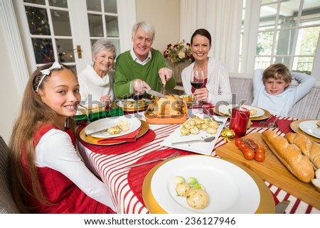 Grandfather carving roats turkey during christmas dinner at home in the living room - stock photo