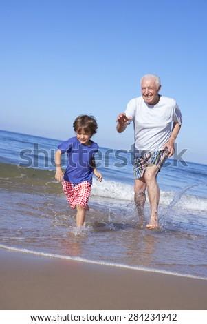 Grandfather Chasing Grandson Along Beach - stock photo
