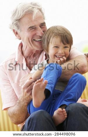 Grandfather Cuddling Grandson On Garden Seat - stock photo