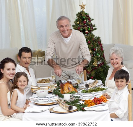 Grandfather cutting turkey for Christmas dinner for his family - stock photo