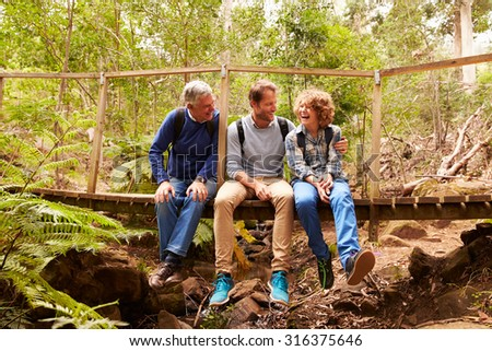 Grandfather, father and son sitting on a bridge in a forest - stock photo