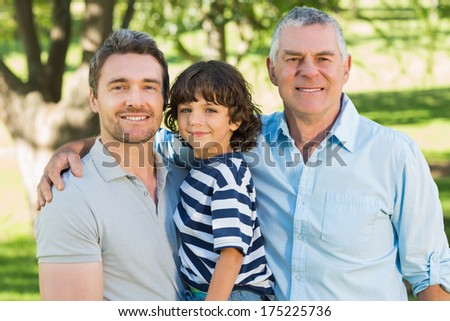 Grandfather father and son smiling against blurred background at the park - stock photo