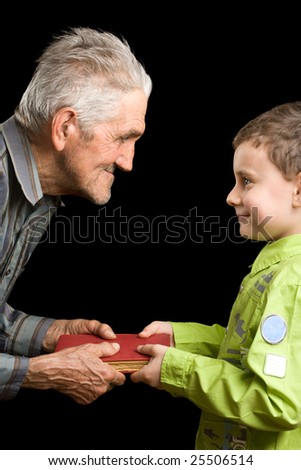 Grandfather giving a book to his grandson - stock photo