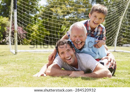Grandfather, Grandson And Father With Football In Garden - stock photo