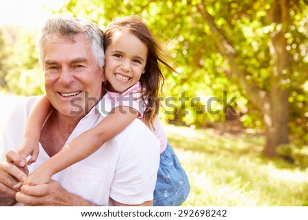 Grandfather having fun outdoors with his granddaughter, portrait - stock photo
