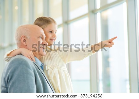 Grandfather holding his granddaughter and communicating. - stock photo