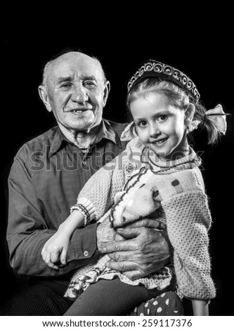 Grandfather holding his granddaughter on his knees - stock photo