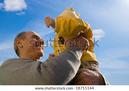 Grandfather holds his granddaughter in hands against the blue sky - stock photo