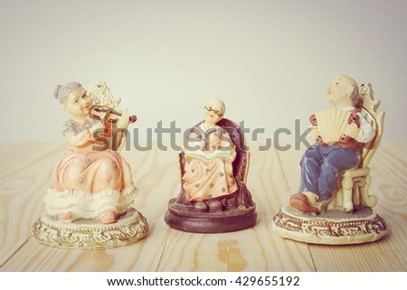 grandfather is playing Accordion with grandmother is playing violin dolls on pine wood background in retro style. -ceramic doll