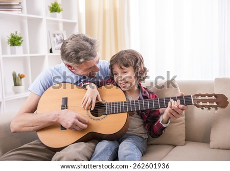 Grandfather is playing guitar with his grandson. - stock photo