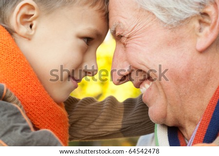grandfather keeps his grandson in an outdoor - stock photo