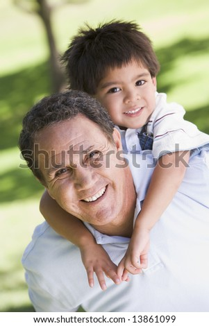 Grandfather piggyback riding grandson - stock photo