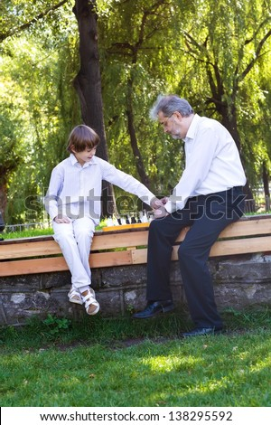 Grandfather playing chess with his grandson - stock photo
